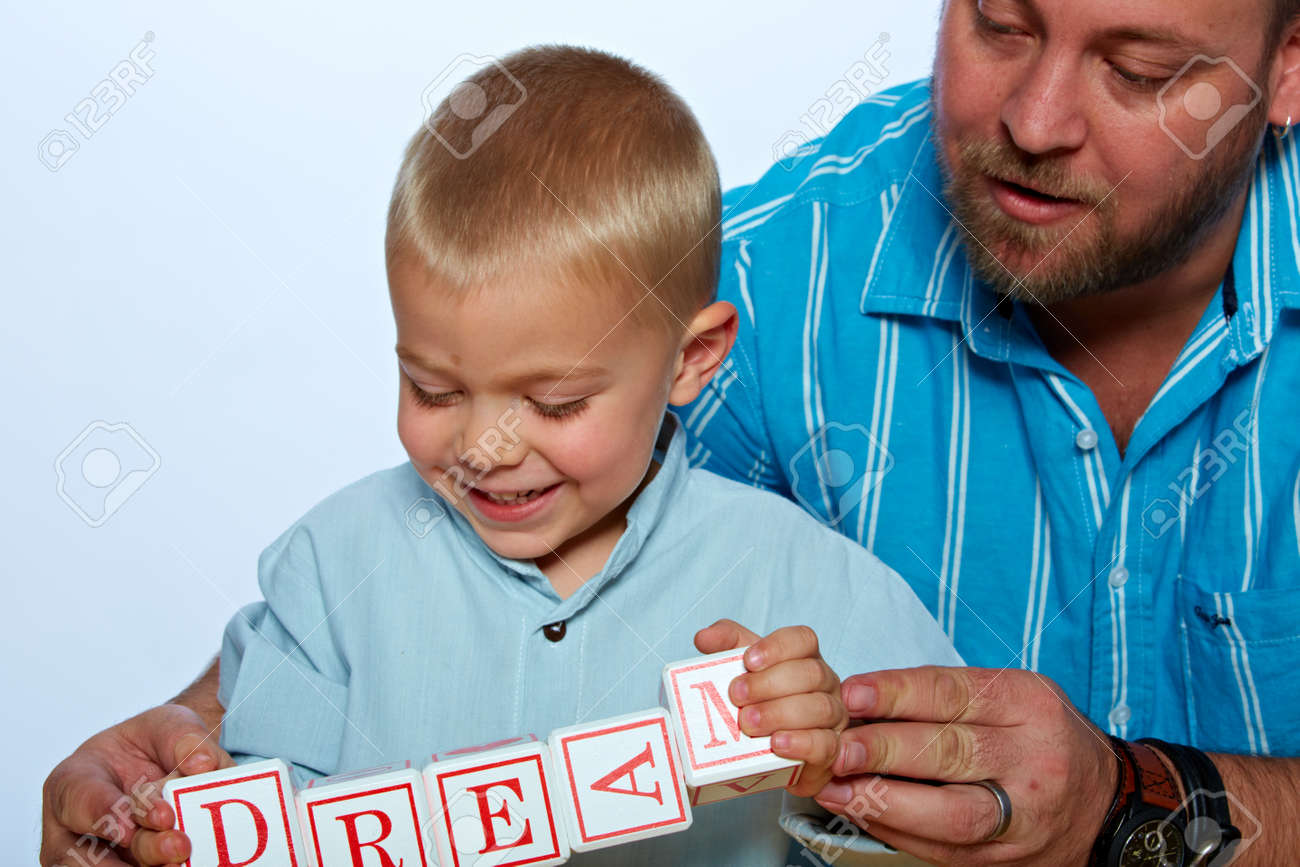 little 3 year old toddler boy and his father playing with wooden abc alphabet blocks on studio background Stock Photo - 14683829
