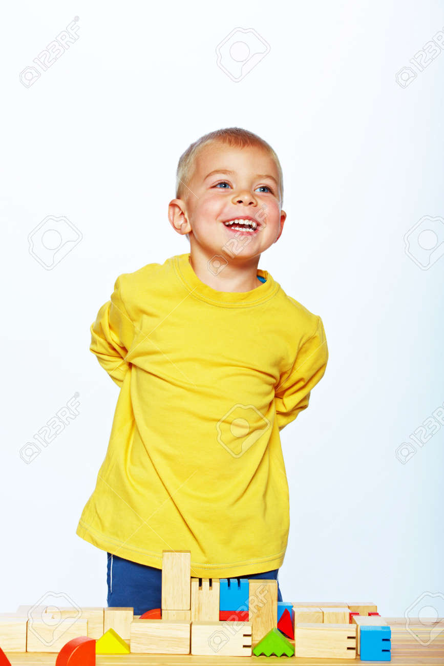 little 3 year old toddler boy playing with bright wooden blocks on a wooden table over white background Stock Photo - 14683814