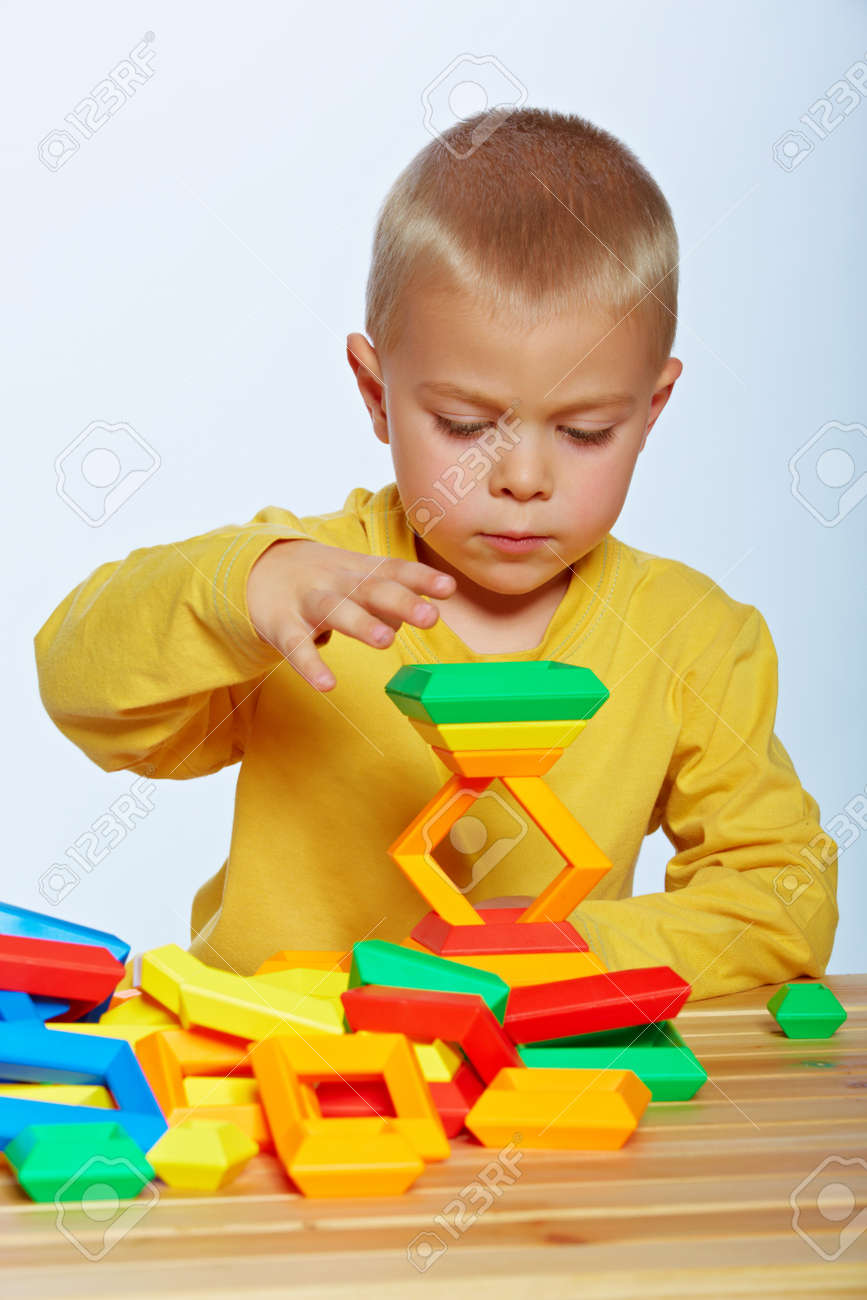 little 3 year old toddler boy playing with bright plastic pyramid blocks over light studio background Stock Photo - 14683825