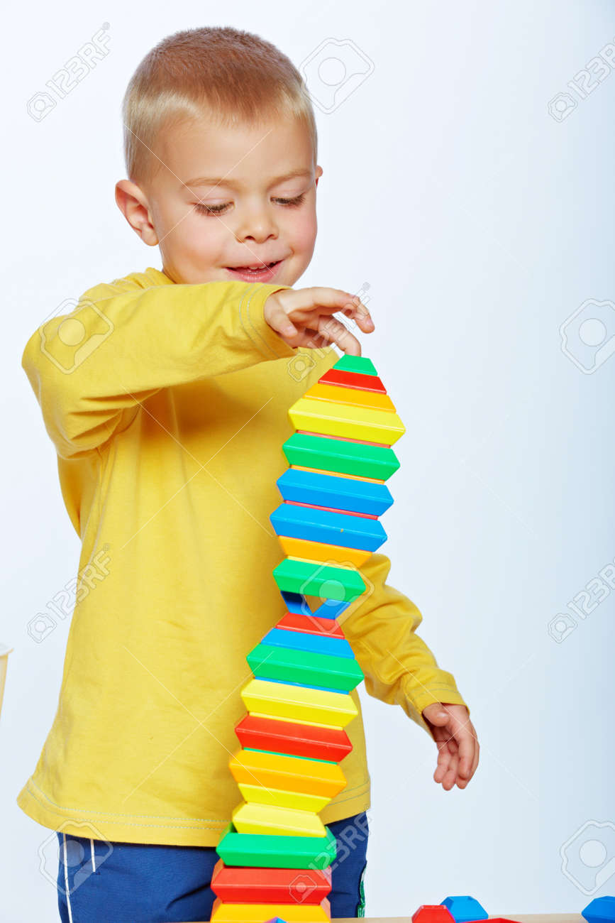 little 3 year old toddler boy playing with bright plastic pyramid blocks over light studio background Stock Photo - 14683824