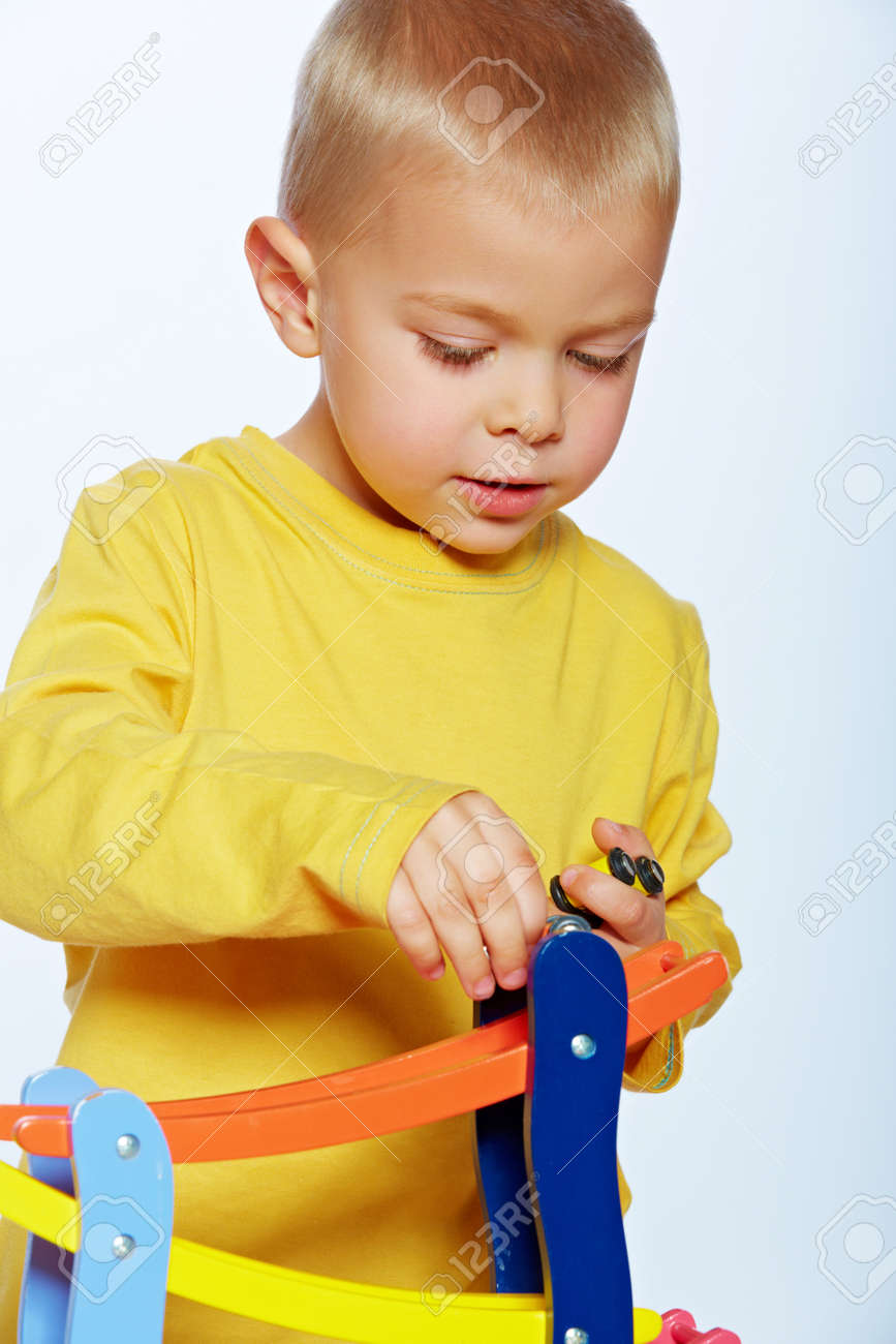 little 3 year old toddler boy playing with wooden cars on studio background Stock Photo - 14683837