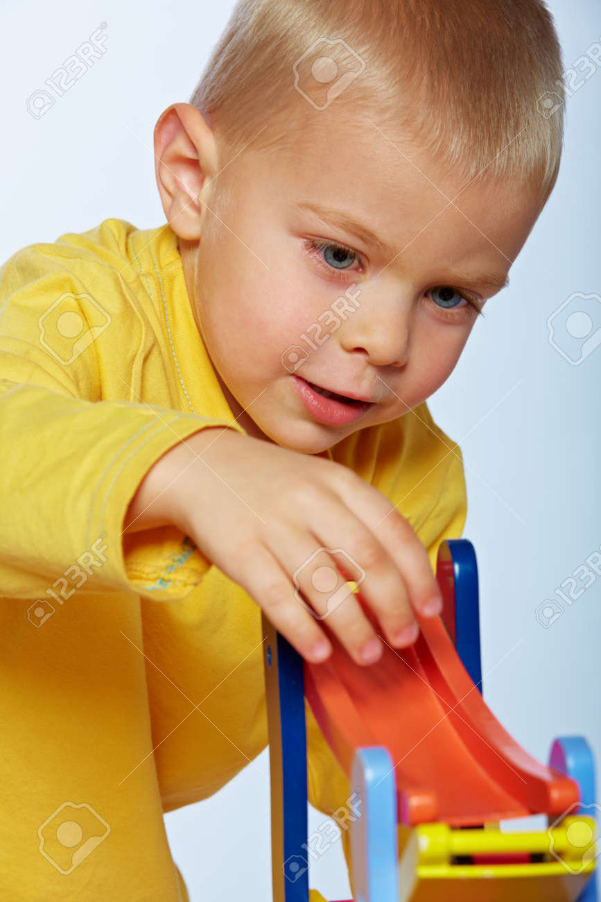 little 3 year old toddler boy playing with wooden cars on studio background Stock Photo - 14683810