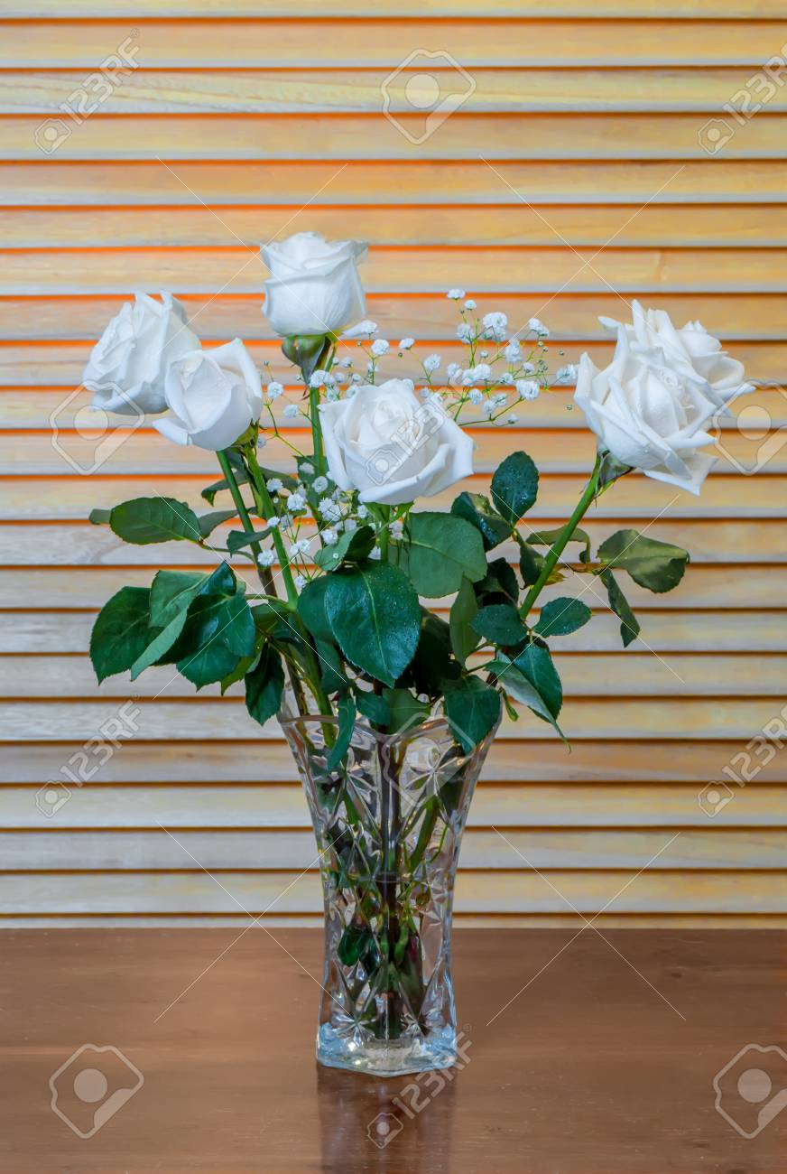 The Plant Is A Bouquet Of White Roses With Green Leaves And Small ...