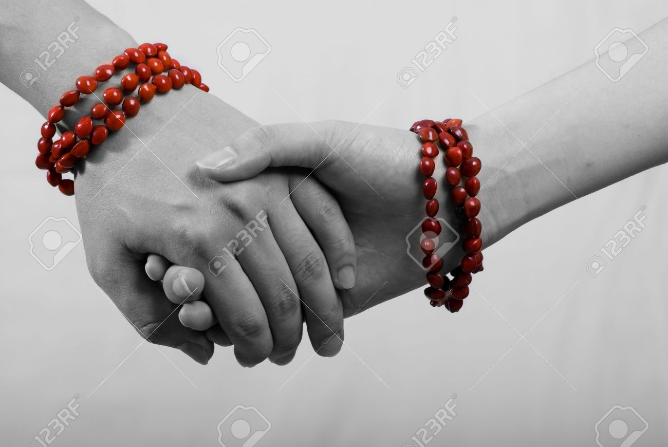 hand in hand with red bracelet in white background - 3276975