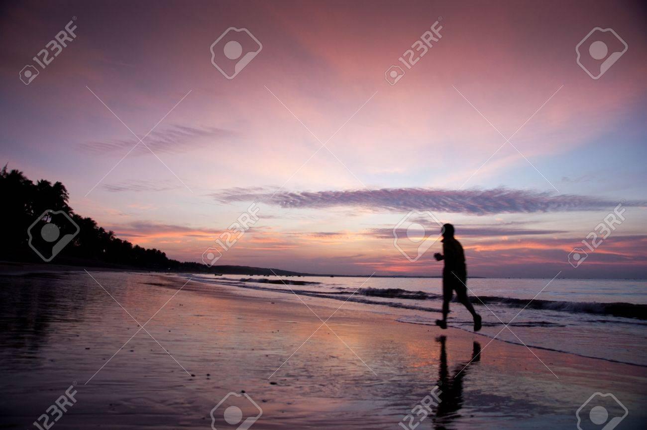 young man run along beach under moring sunrise - 6274443