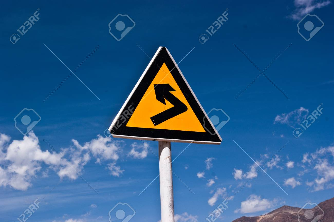 turning sign on yellow metal signboard against blue sky - 7481448