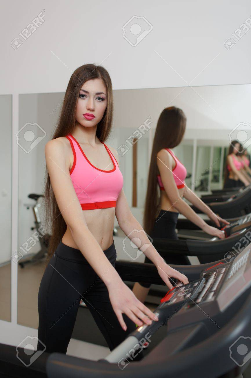 Sexy brunette with long hair and sporting appearance posing in the gym. Young fitness woman in pink t-shirt trainers at the gym. - 36902808