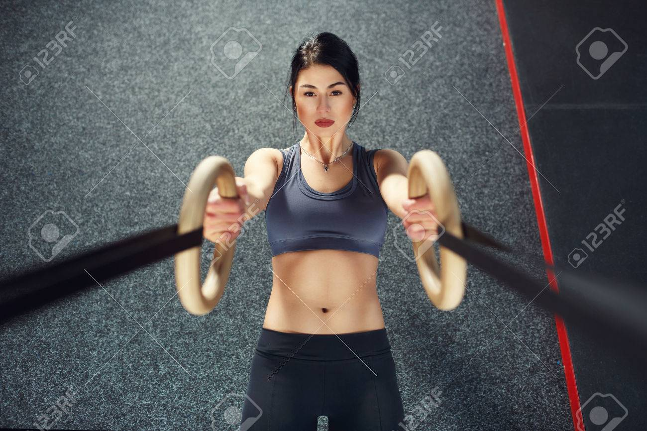 Crossfit workout on ring. Fitness woman holds training session crossfit on the rings in the gym. Muscular woman Caucasian appearance, brunette, is engaged in the gym - 38651160