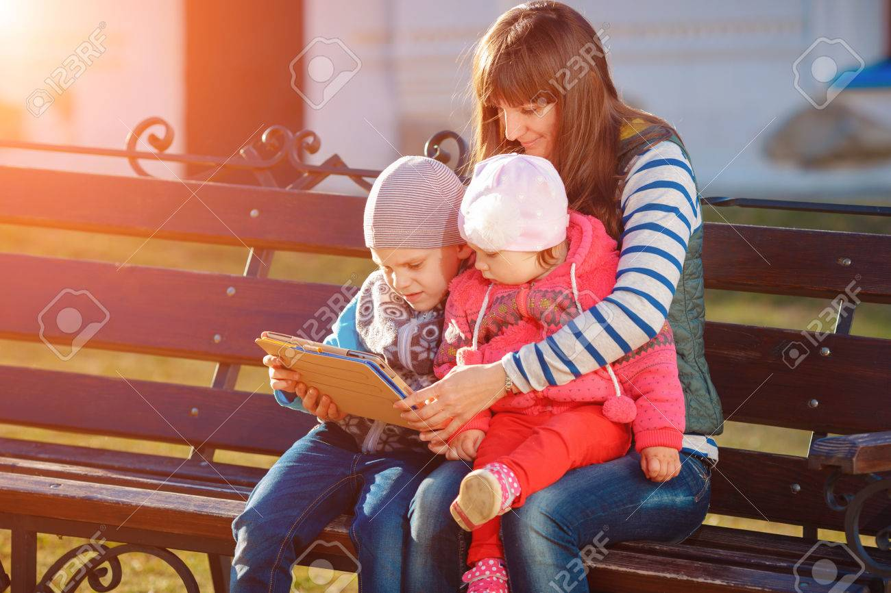 Happy family of three, mother, son and daughter sitting on a bench in the afternoon in the city park and are holding a tablet, a beautiful spring weather, the sun is shining - 39283566