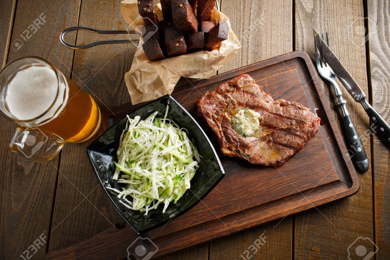 Delicious fried steak with butter and herbs, black plate of salad with fresh cabbage, beer and rye toast on dark wooden - 39535174