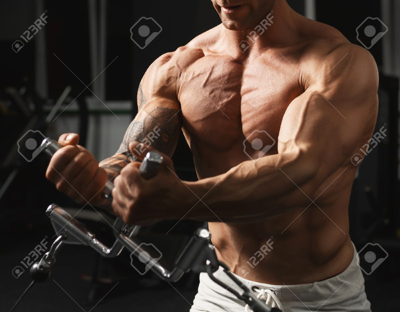 Strong muscular bodybuilder doing exercise on the chest in the crossover in the gym - 41670028