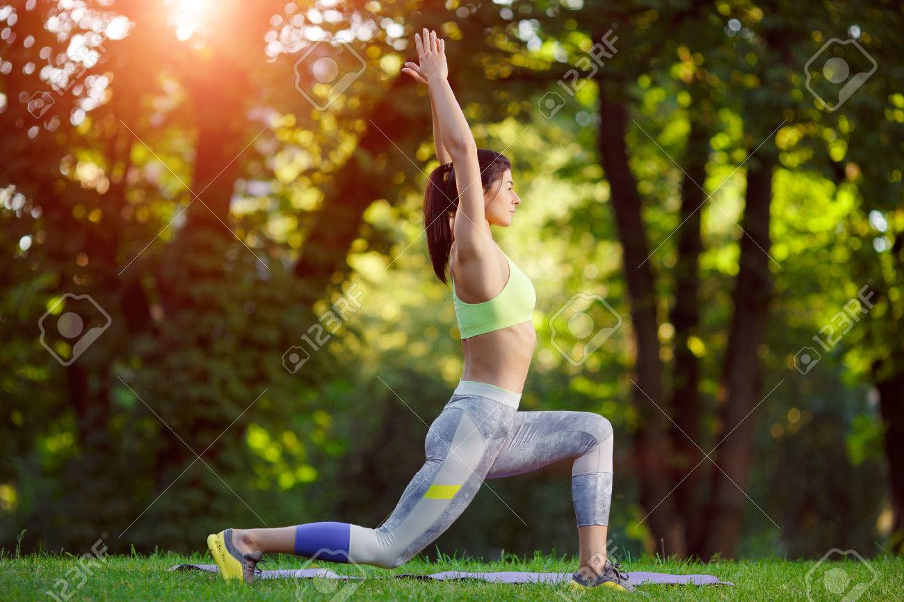 Young smiling woman doing fitness exercises in the park on the green grass. Fitness training in the sunlight. - 43152812