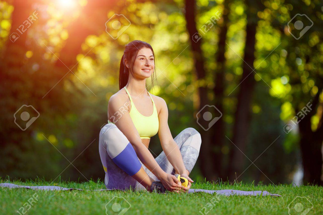 Young smiling woman doing fitness exercises in the park on the green grass. Fitness training in the sunlight. - 43152820