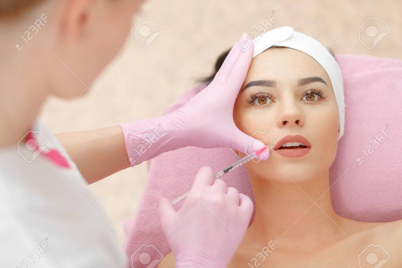 Beautiful woman gets injection in her lips. - 58918095