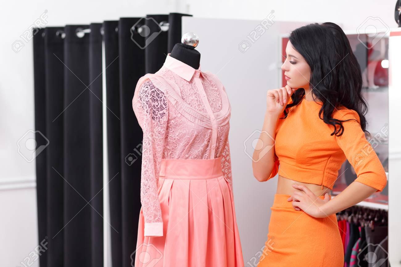 352b11fe34 Compras De La Mujer Para El Vestido En La Tienda De Ropa. Chica De  Compradores Caucásico Elegir Vestido De Color Rosa En La Tienda ...