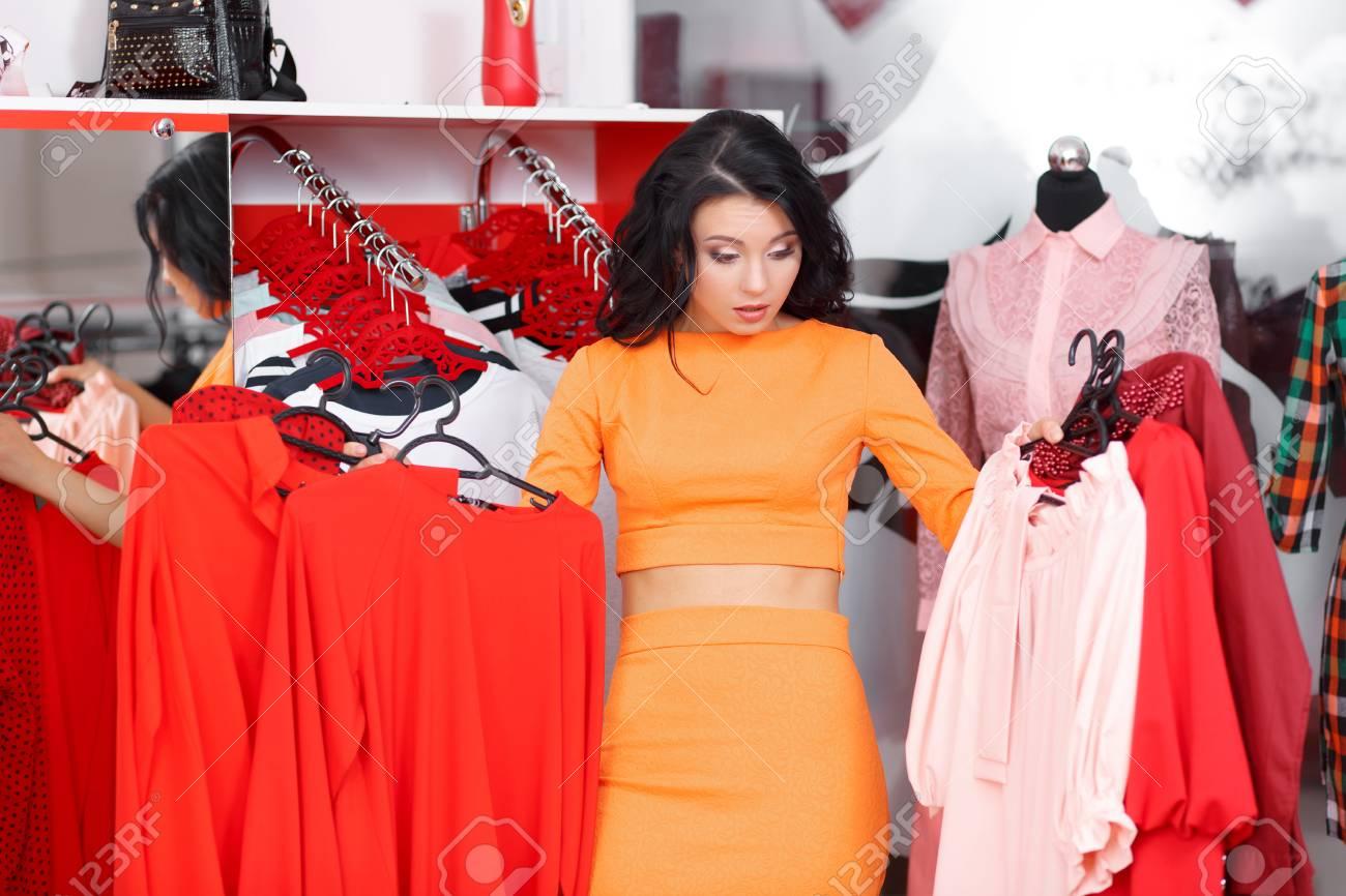 dce05b297d Femme Shopping Pour La Robe Dans Le Magasin De Vêtements. Caucasien,  Shopper, Girl, Choisir, Robe Rouge, Dans, Magasin, Pendant, Vente.