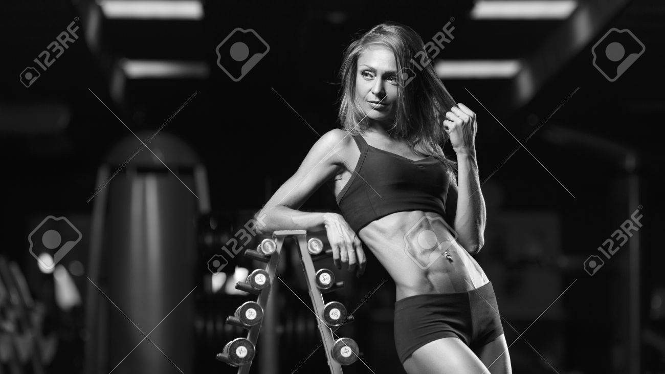 Black and white photo fitness woman posing in the gym perfect