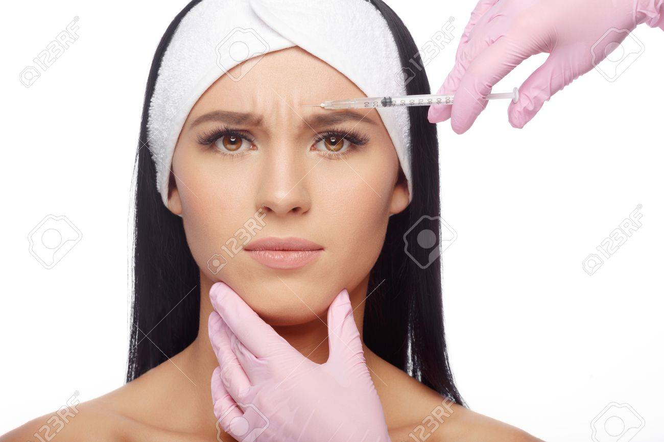Beautiful woman getting lifting injection in forehead. Close-up woman hyaluronic acid injection. Injections of skin rejuvenation. Cosmetic procedures, injections, hyaluronic acid. - 63480265
