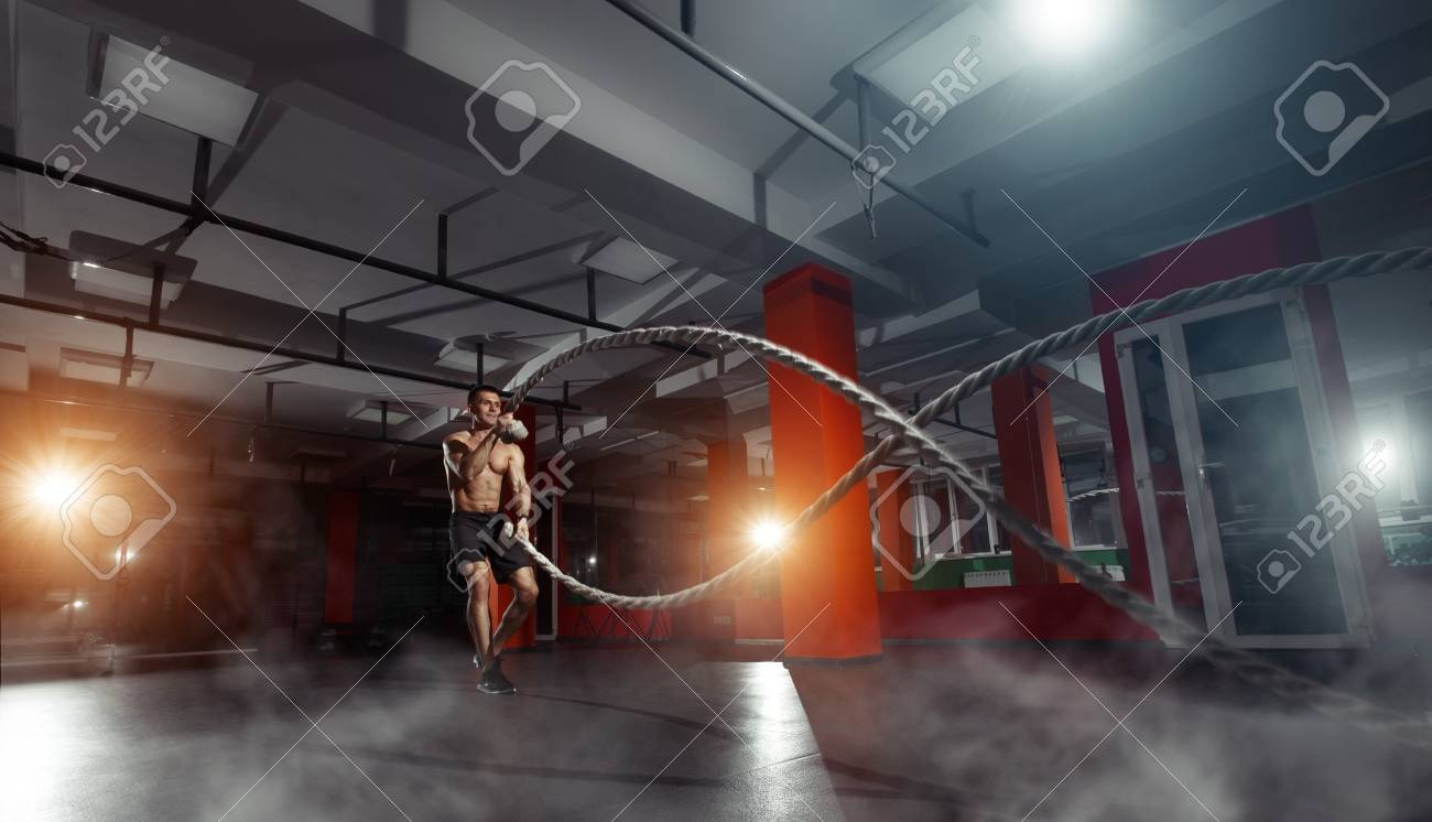 Fitness man working out with battle ropes at gym. Battle ropes fitness man at gym workout exercise fitted body. Fitness man training with battle rope in fitness club. Training with battle rope - 66304161