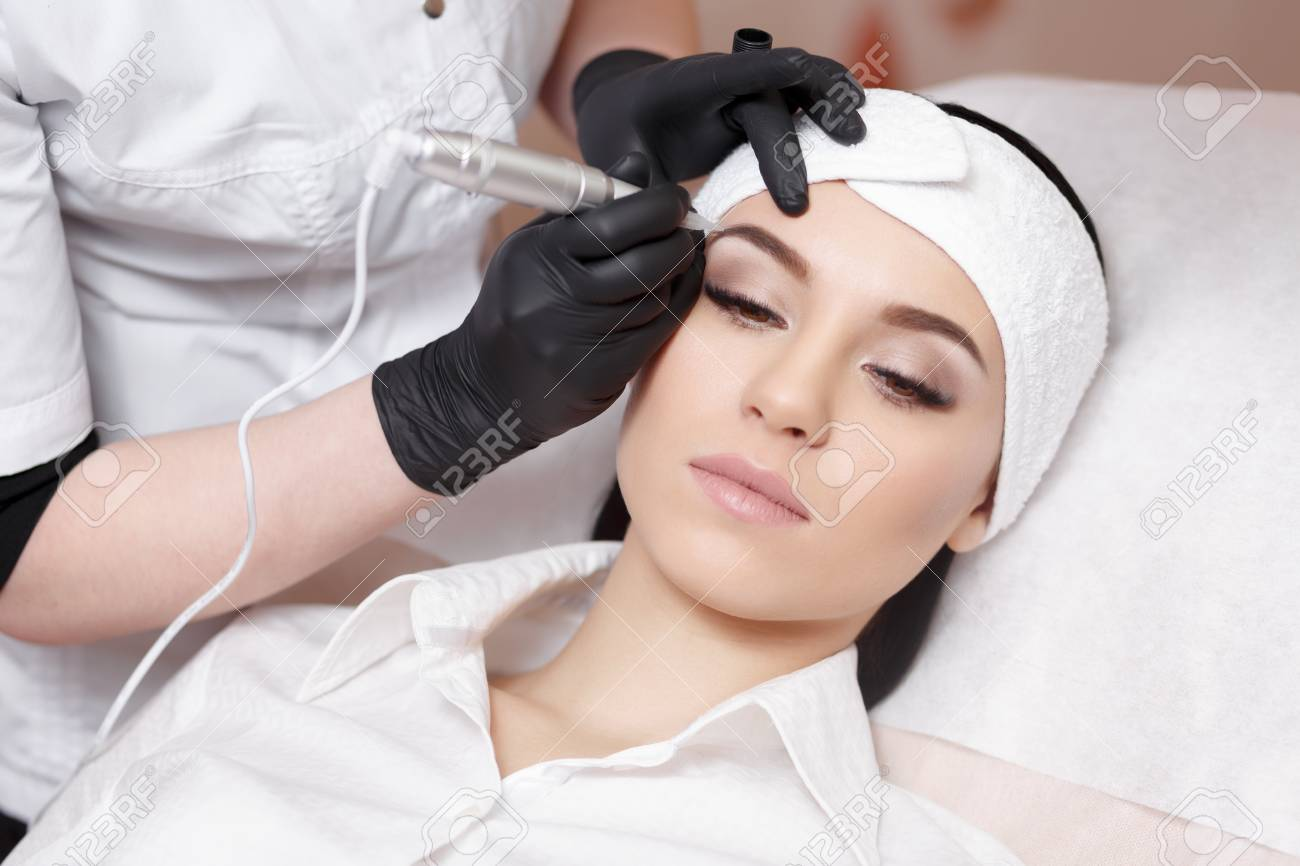 Permanent makeup. Permanent tattooing of eyebrows. Cosmetologist applying permanent make up on eyebrows- eyebrow tattoo - 67275688
