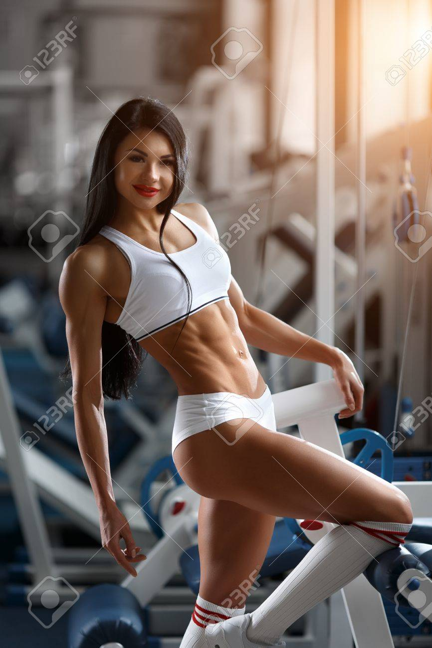 65983e242 Beautiful sports young woman posing in fitness gym. Fitness girl in white  sportswear. Muscular
