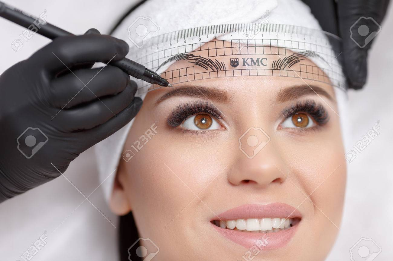 Permanent makeup eyebrows. Mikrobleyding eyebrows workflow in a beauty salon. Cosmetologist applying a special