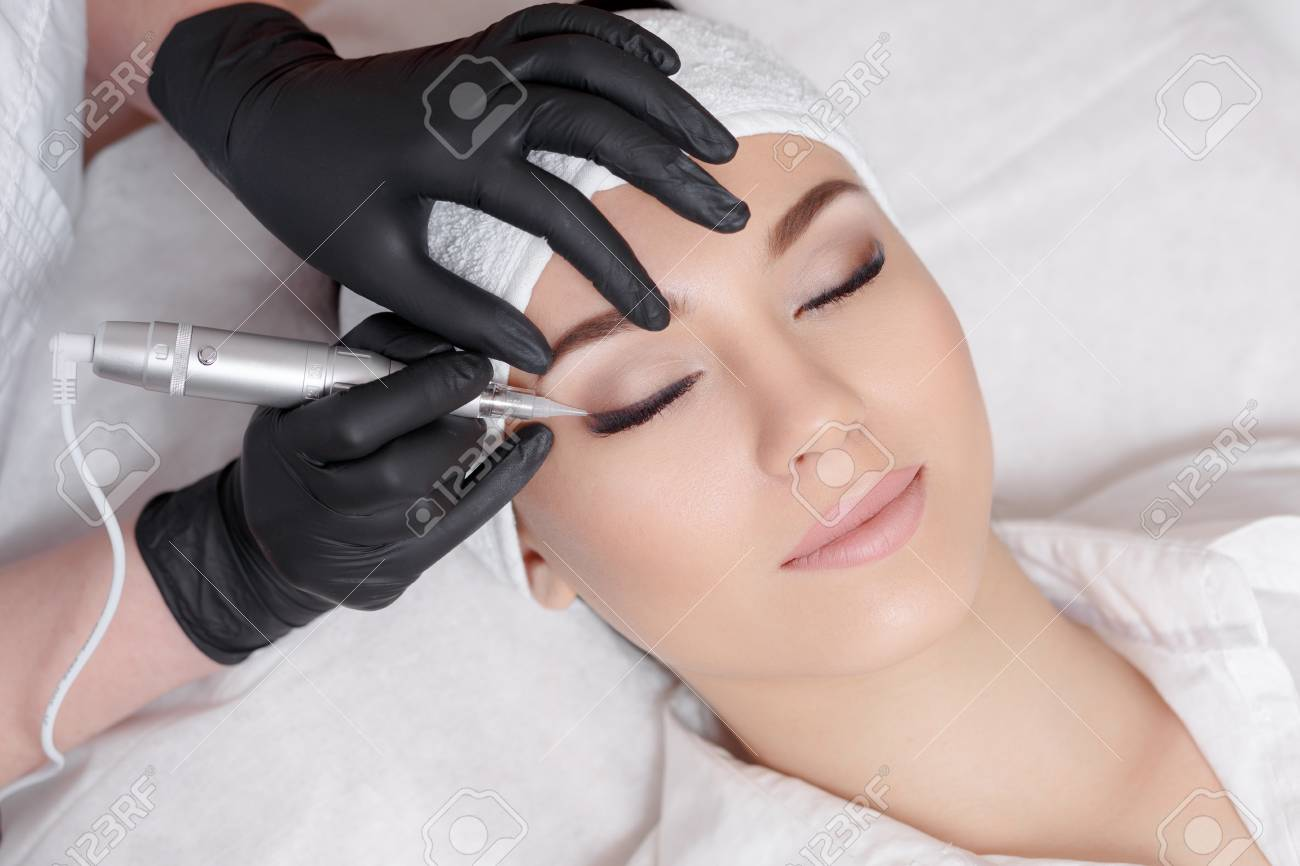 Professional cosmetologist wearing black gloves making permanent makeup - 70202484