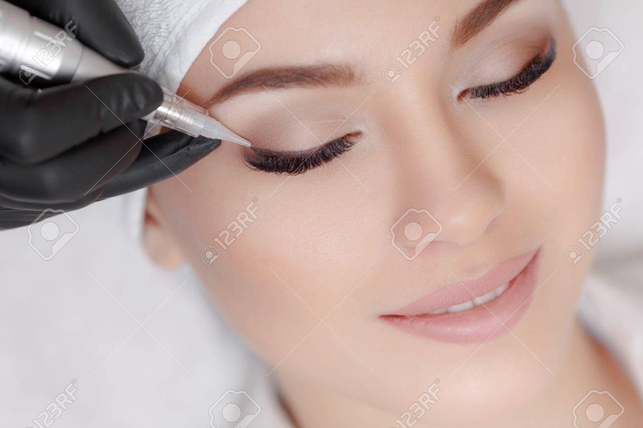 Cosmetologist making permanent make up at beauty salon - 69336551
