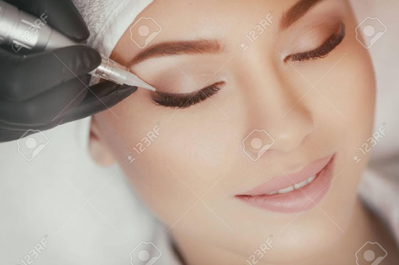 Cosmetologist making permanent make up at beauty salon - 70266328