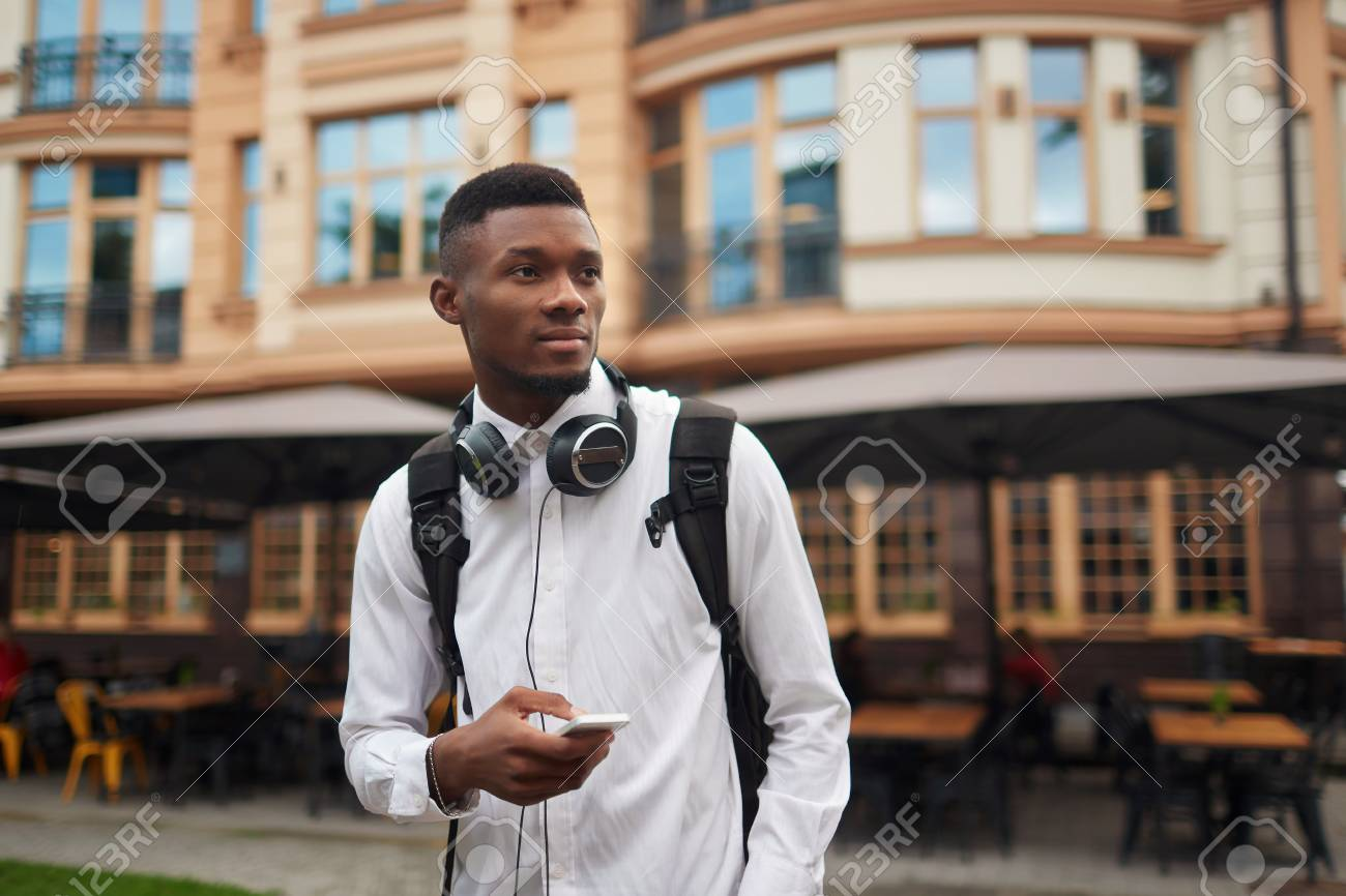 African male walking and searching location in smart phone. - 87555462