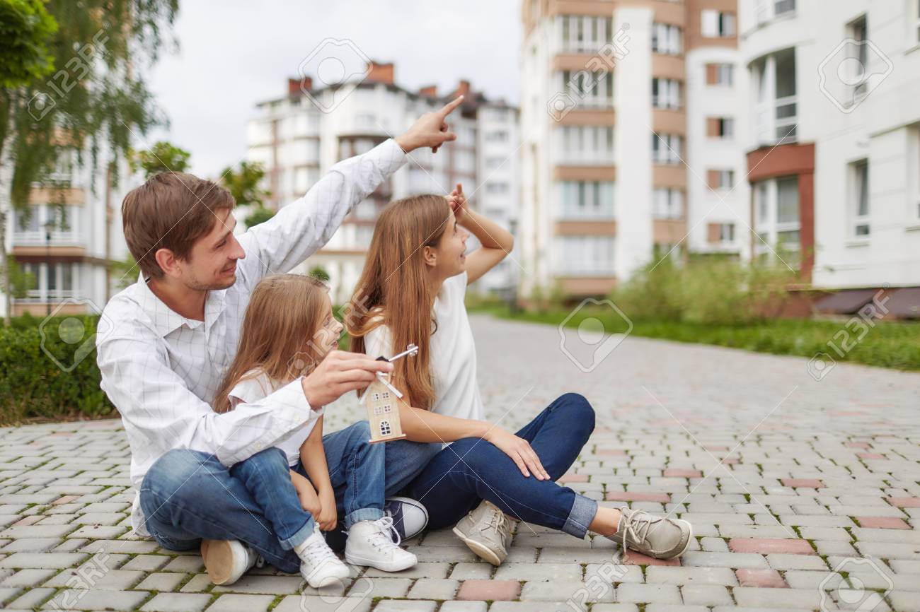Happy family in front of new apartment building - 88269149