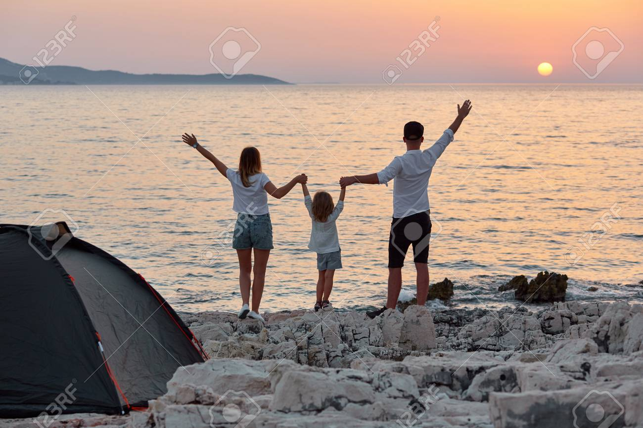 Back view of sweet young family, standing with open hands on rock beach and enjoying setting sun over sea. Mom, dad and little daughter holding hand and having best time together at summer vacation. - 106357560