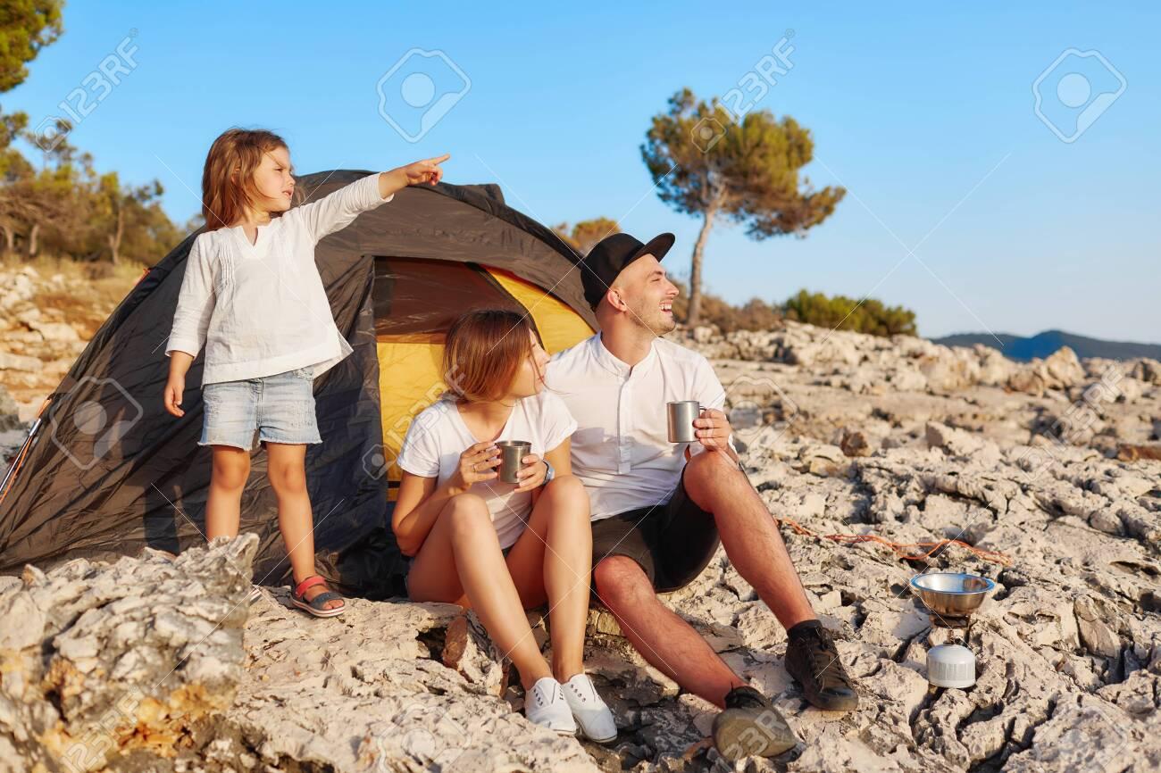 Family sitting near tent at rock beach admiring summer vacation. - 122905195