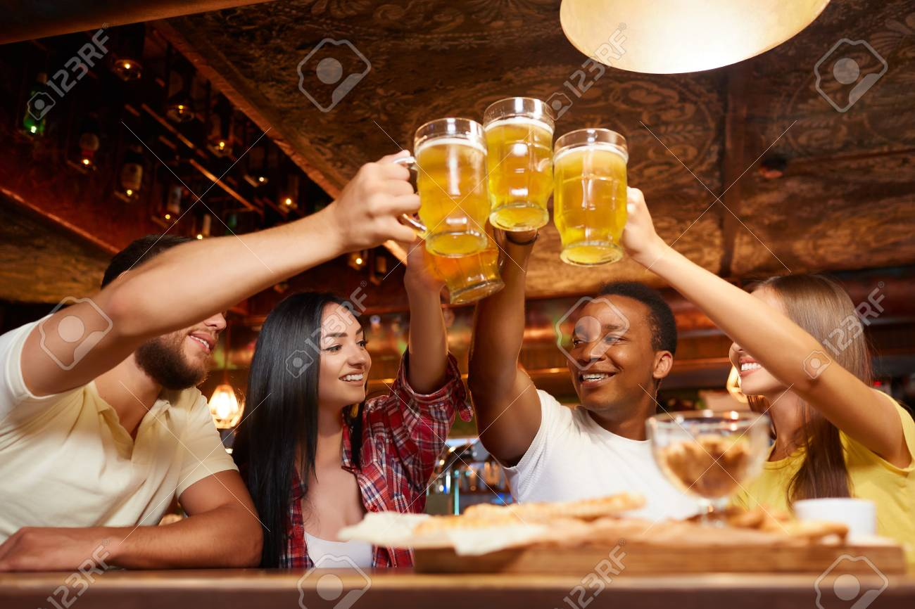 Four boys and two girls having fun together, raising beer above table. - 107927664