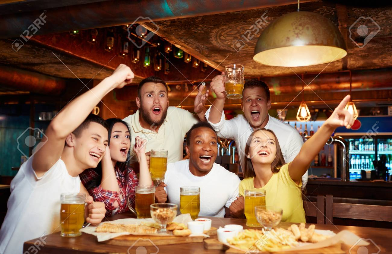 Happy friends having fun in pub watching sport in TV together. - 107927688