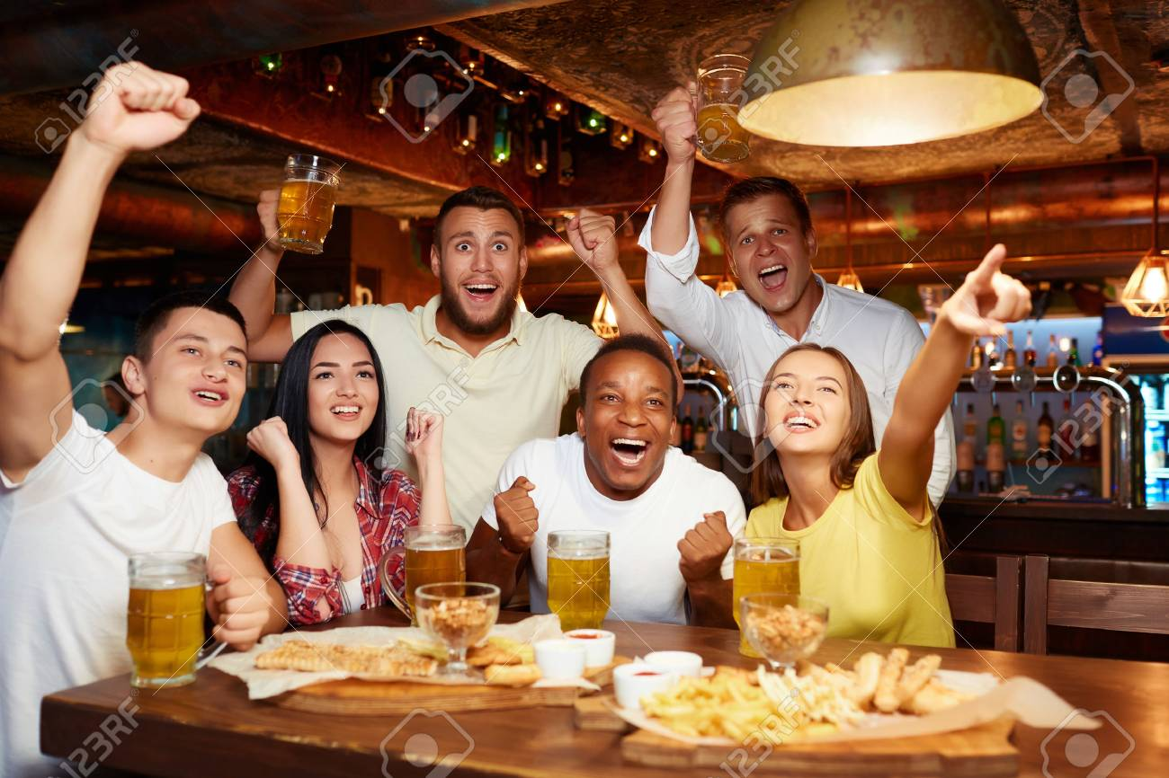Happy friends having fun in pub watching sport in TV together. - 107927691