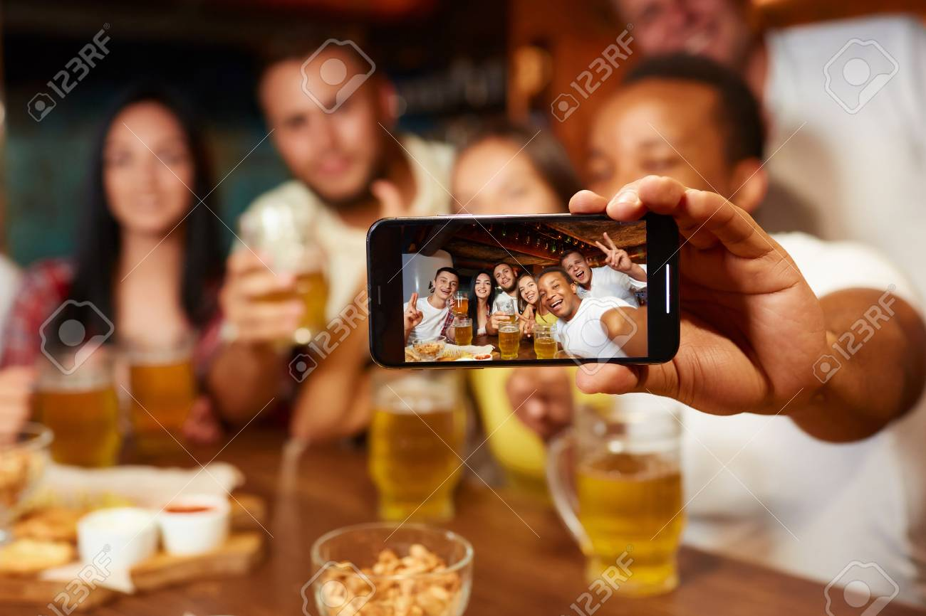 Group of funny friends taking self portrait in bar. - 107927695