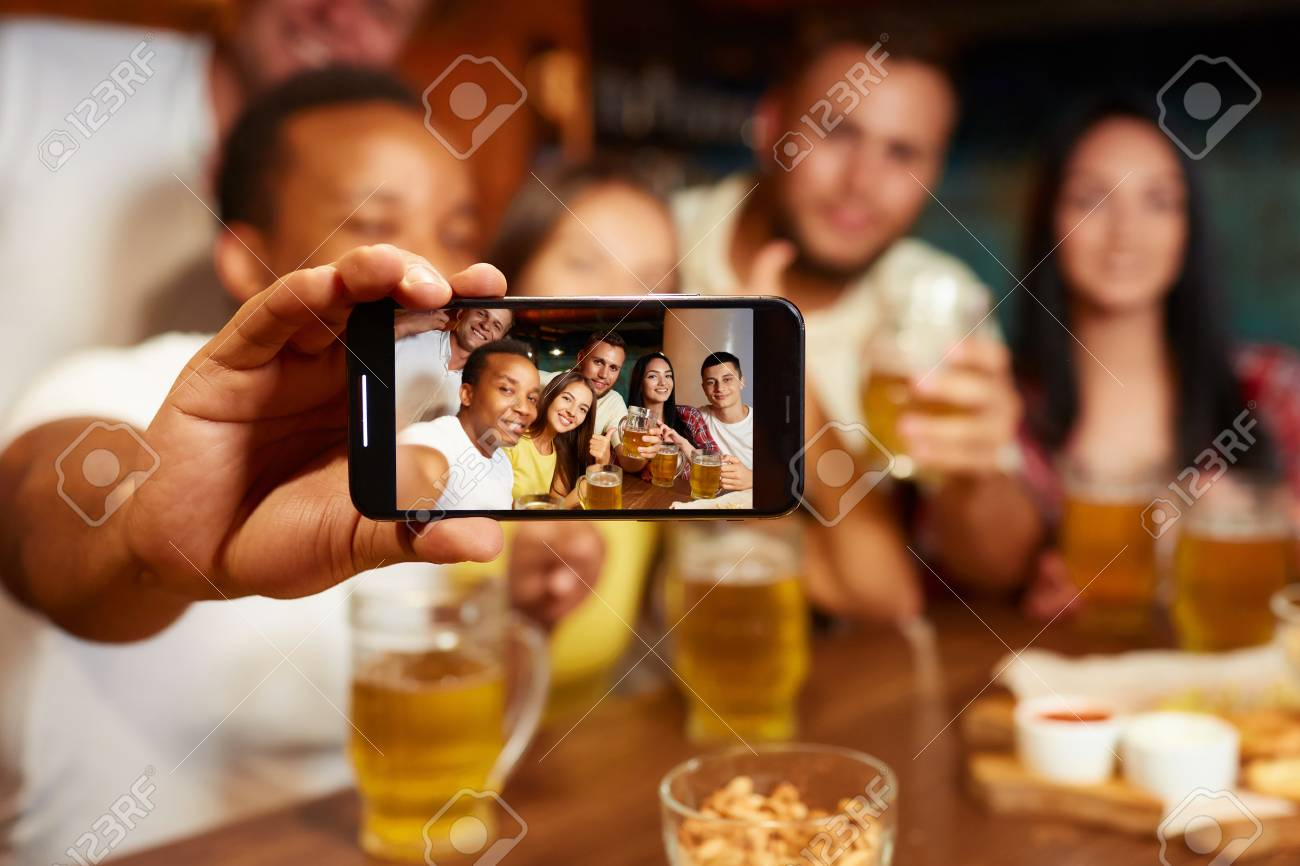 Group of funny friends taking self portrait in bar. - 107927735