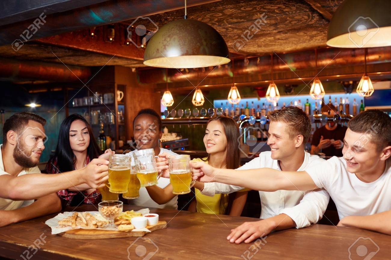 Smiling group of friends enjoying beer at pub, toasting and laughing. - 107927752