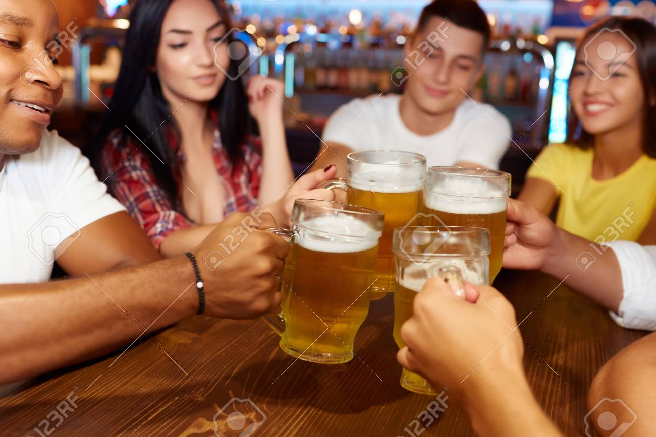 Group of happy friends enjoying beer at pub, toasting and laughing. - 107927764