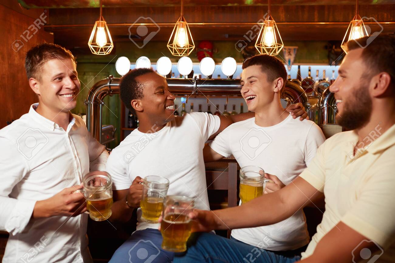 Company of four handsome men holding glass of beer, smiling and embracing. - 122913406