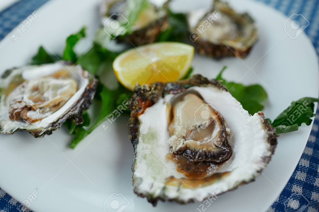 Fresh oysters on a white plate with green salad and lemon on a blue tablecloth - 126906733