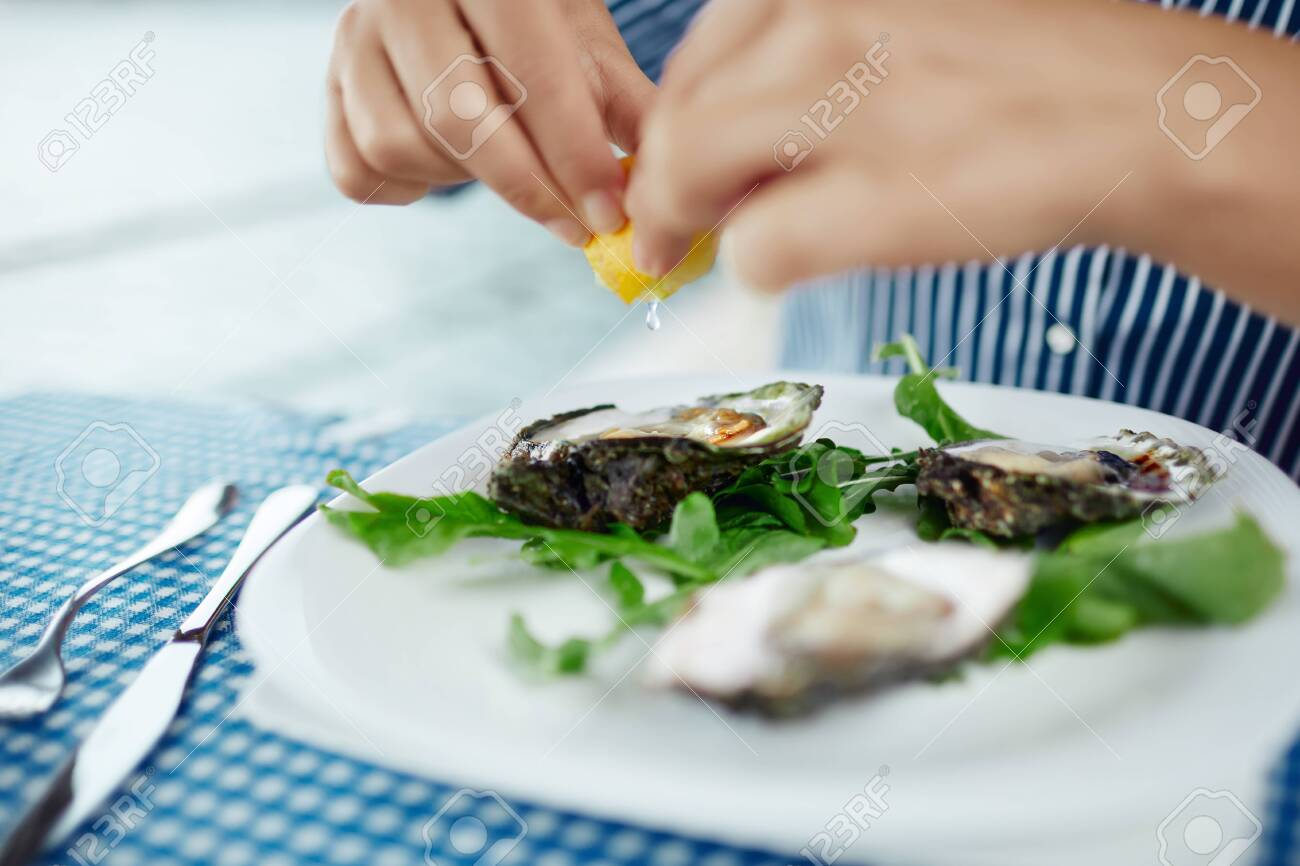 Womens hands squeezing lemon juice on raw oyster, close up - 122913410