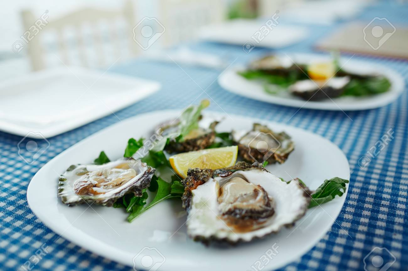 Fresh oysters on a white plate with green salad and lemon on a blue tablecloth - 126906734