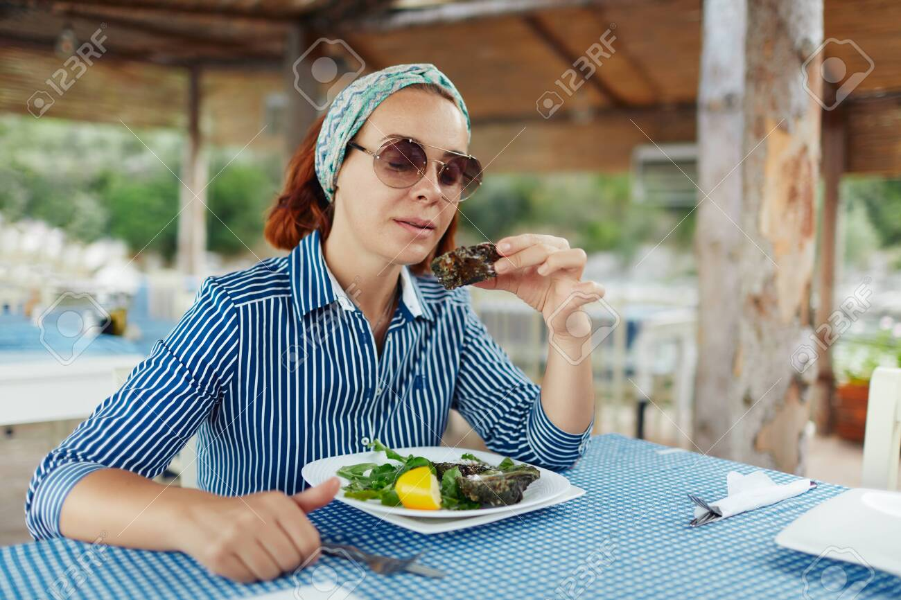 Young woman eating oyster in an outdoor restaurant - 122913415
