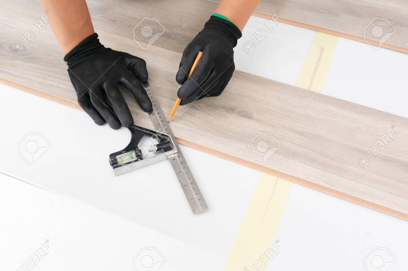 Worker hands installing timber laminate floor. - 144172765
