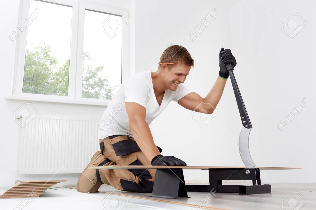 Worker cut wooden batten for laminate floor, floating wood tile - 143426213