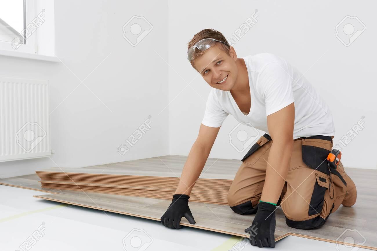 Man installing new wooden laminate flooring - 143961647
