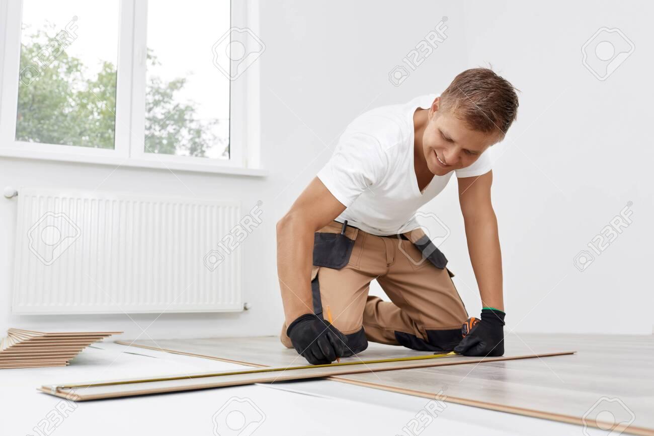Man installing new wooden laminate flooring - 143965654