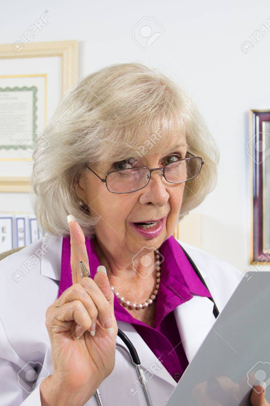 A woman doctor sitting at her desk appears to be giving a warning on a medical subject. Stock Photo - 15599975